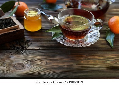 Cup of black tea, tea leaves, honey and tangerines on the wooden background with copy space. Horizontal. Daylight. Close-up.