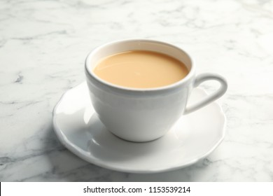 Cup with black tea and milk on marble table