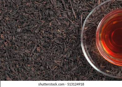 A cup of black tea on a background of black tea