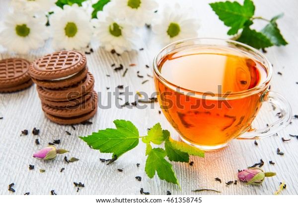 A cup of black tea on a background of daisies and greenery