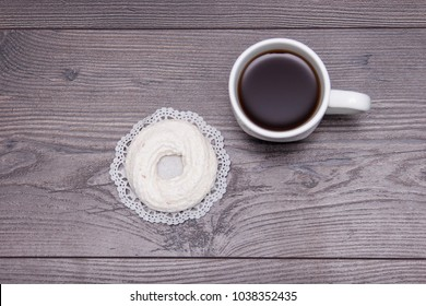 Cup of black tea with tasty delicious merengue on the brown wooden table, top view