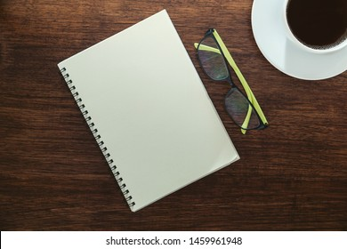 A cup of blackcoffee , blank notepad and eyeglasses on wooden table workpalce, top view.