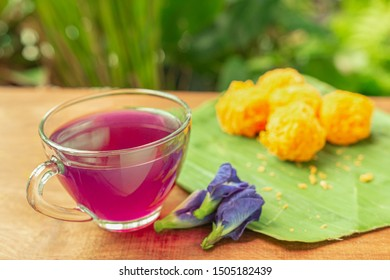 Cup of Blue pea drink or Butterfly pea flower for healthy drinking with Thai traditional dessert. Health drink concept. Selective focus.