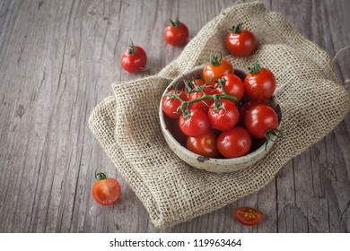 Cup with a bunch of fresh tomatoes on a wooden table