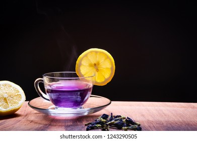 Cup of Butterfly pea flower tea with lemons on wooden background. Health drink concept.