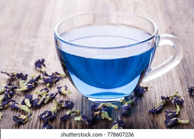 Cup of Butterfly pea tea (pea flowers, blue pea) for healthy drinking, detox drinking on old wooden table