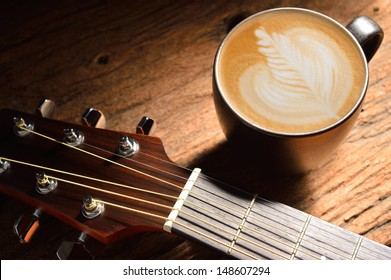 A cup of cafe latte and guitar on wooden table