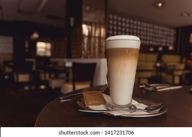 Cup of caffe latte with set of cutlery on brown table in coffeehouse