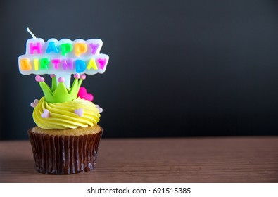 Cup cake and happy birthday text candle  on  cupcake .Birthday cupcake with a happy brithday text candle.Cupcake with yellow cream and heart for love valentines.green crown