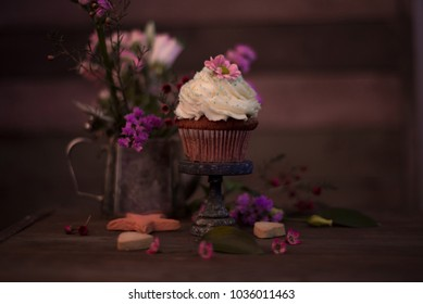 Cup cakes with cream cheese topping on beautiful wooden cake stand with flowers and wooden background behind it, spring mood still life photo for holiday design