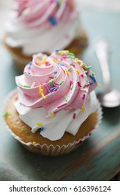 cup cakes with vanilla and strawberry cream and sprinkles