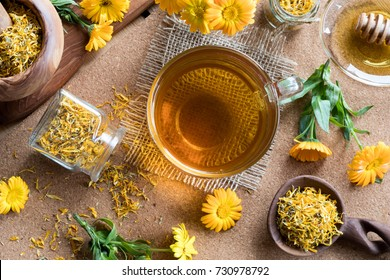 A cup of calendula (marigold) tea on a table, with fresh and dry calendula flowers in the background, top view