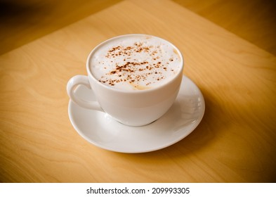 a cup of cappucchino over wooden table