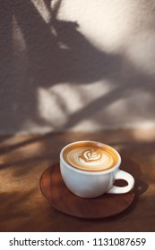 Cup of cappuccino with beautiful heart shape latte art. Tropical and hipster vibes. Plants shadows. Sul lights and shadows.