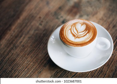 Cup of cappuccino with beautiful latte art on wooden table. Flat lay style.