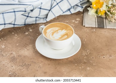 Cup of cappuccino with a beautiful pattern on an abstract textured background