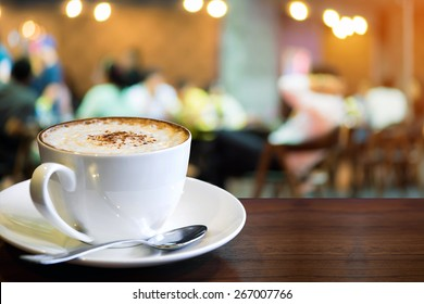 Cup of cappuccino with blur coffee shop background