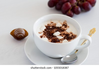 Cup of cappuccino with cocao and marshmallows on white wooden background
