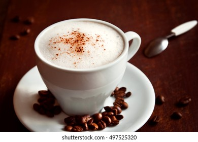 Cup of cappuccino coffee with cacao topping over dark rustic wooden background
