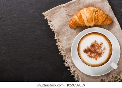 Cup of cappuccino coffee and croissant on dark table, top view