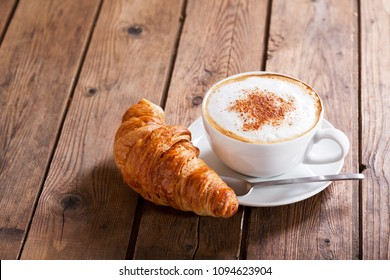 Cup of cappuccino coffee with croissant on wooden table