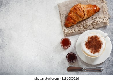 Cup of cappuccino coffee with croissant, top view
