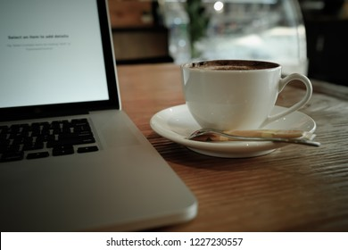 A cup of cappuccino coffee with laptop on table. Royalty high quality free stock image of capuccino coffee with laptop for working in a coffee shop. Beautiful workspace with retro and vintage style