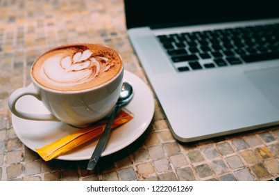 A cup of cappuccino coffee or latte coffe in a white cup with laptop on table. Royalty high quality free stock photo of drink capuccino or latte coffe with laptop for working in office