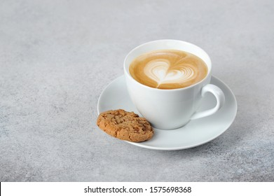 Cup with cappuccino coffee. Milk foam depicts a heart. Oatmeal cookies on a saucer. Free space for text. Light background.