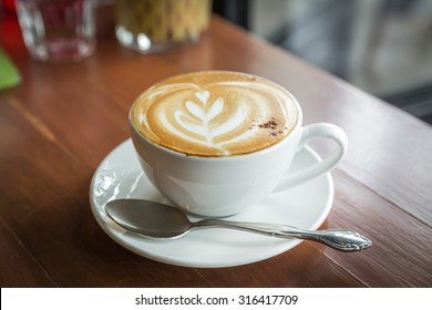 cup of cappuccino, cup of coffee on brown wooden table