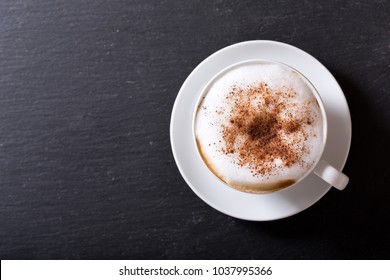 Cup of cappuccino coffee on dark table, top view