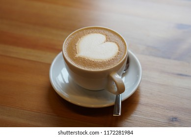 Cup of cappuccino coffee on a table in a cafe. Close up cappuccino in ceramic cup. Cappuccino coffee with milk. Cup of fresh cappuccino with heart sign.