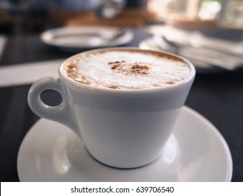A cup of cappuccino coffee on the table in restaurant, soft focus, vintage tone