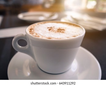 A cup of cappuccino coffee on the table in restaurant, soft focus, warm tone