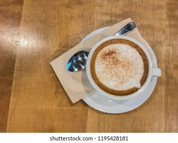 Cup of cappuccino coffee on wood table
