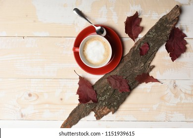 Cup of cappuccino coffee on wooden background with autumn leaves and bark of tree. Autumn mood concept. Warm and cozy autumn coffee time. Red ceramic tableware with tasty beverage, top view.
