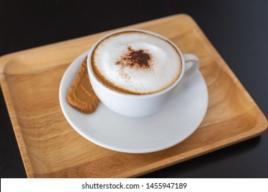 Cup of cappuccino coffee on wooden tray and table. select focus