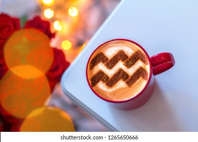 a cup of cappuccino coffee with a pattern of the aquarius zodiac sign on milk foam