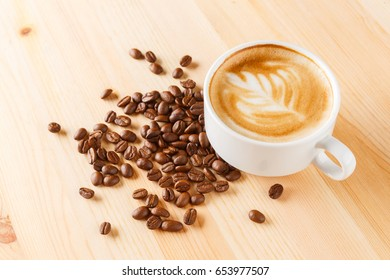 Cup of cappuccino coffee with raw and roasted beans on pine wood table