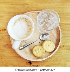 A cup of cappuccino coffee served with two biscuits, a glass of cold water and one coffee spoon, on the wooden tray. With background of wooden top table