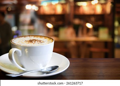Cup of cappuccino with coffee shop background