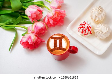 a cup of cappuccino coffee with a twin zodiac sign symbol