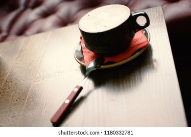 Cup of cappuccino in dark cafe on wooden table shot with copyspace