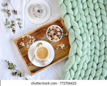 Cup with cappuccino, doughnutt, green pastel giant plaid, bedroom, morning concept, top view