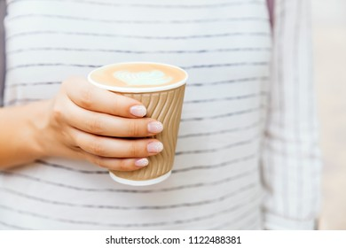 Cup of cappuccino in female hand with fashion manicure.