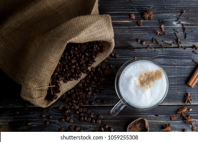 Cup of cappuccino with foam, Coffee beans on the wooden background, jute bag and spices