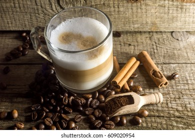 Cup of cappuccino and grain of coffee over wooden background