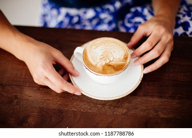 Cup of cappuccino in hands.
