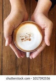 a cup of cappuccino in hands on brown wooden background