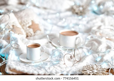 Cup of cappuccino or hot chocolate , cacao with christmas decoration like it  slippers, stars and lights on the table. White and blue colors. Bedroom background. Winter style photo